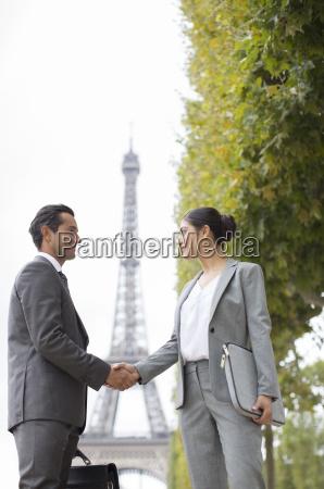 business people shaking hands near eiffel