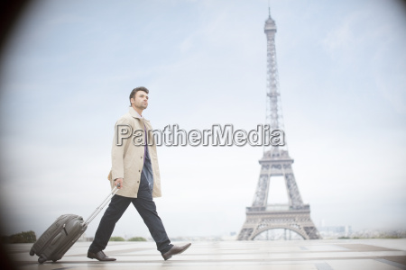 businessman pulling suitcase near eiffel tower