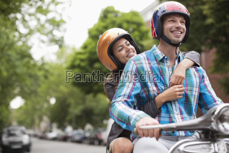 couple riding scooter together outdoors