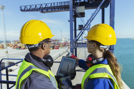 workers using digital tablet on cargo
