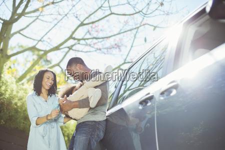 glueckliche familie ausserhalb auto