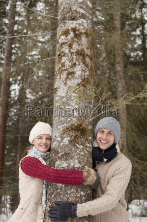 portrait of happy couple hugging tree