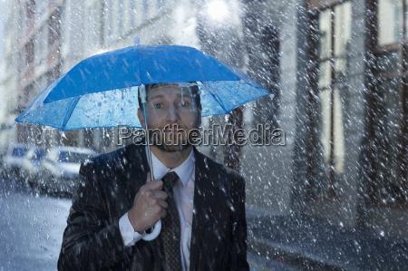 portrait of businessman with tiny umbrella