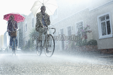 couple with umbrellas riding bicycles in