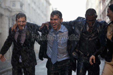 happy businessmen walking in rainy street