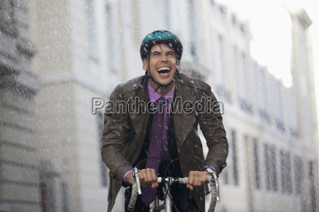 enthusiastic businessman riding bicycle in rain