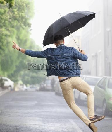 man dancing with umbrella in rainy