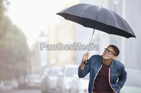 man with umbrella looking up at