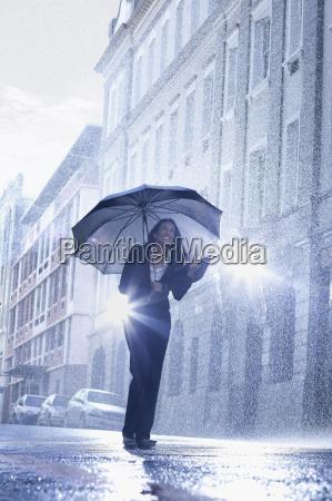 businesswoman standing under umbrella in rainy