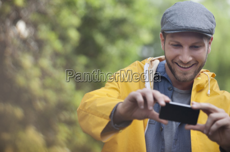 happy man taking photograph with camera