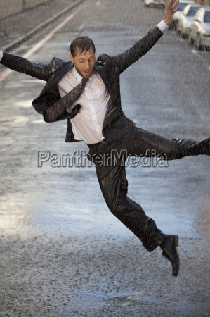 enthusiastic, businessman, dancing, in, rainy, street - 17155760