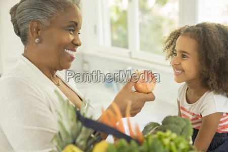 happy grandmother giving apple to granddaughter