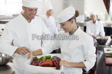 chefs examining vegetables in restaurant kitchen