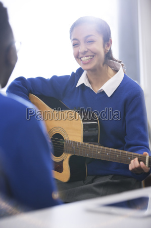 smiling female student playing acoustic guitar