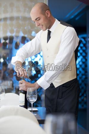 waiter uncorking bottle of wine in
