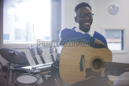 smiling college student sitting with acoustic
