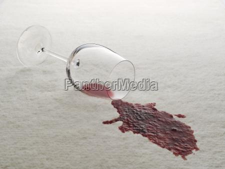 glas rotwein verschuettet auf weissem teppich