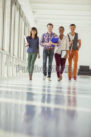 portrait of creative business people walking