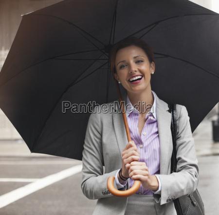 businesswoman holding umbrella on city street