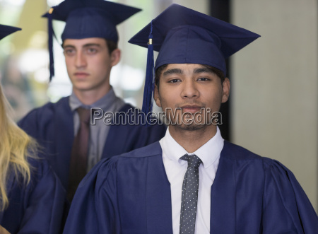male student in graduation clothes looking