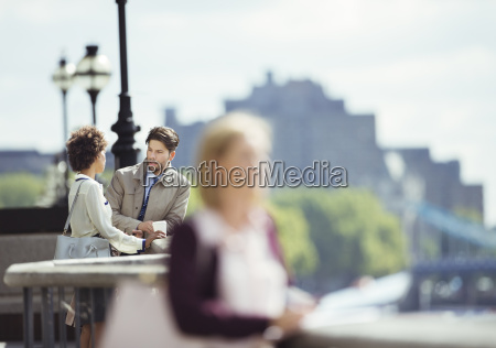 business people talking on city waterfront