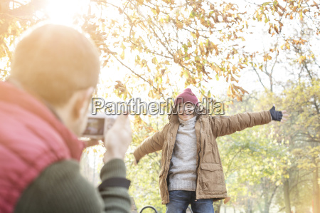 father photographing daughter in sunny autumn