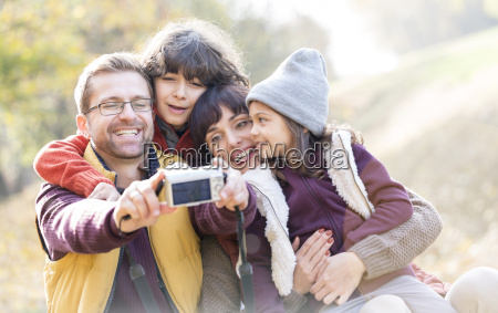 smiling family taking selfie with digital