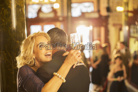 enthusiastic woman with champagne hugging man