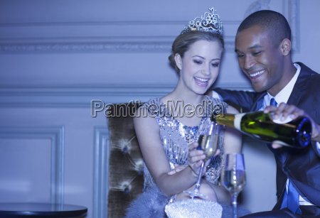man pouring champagne for woman in