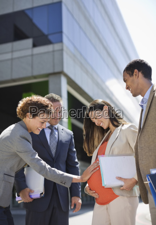 businesswoman holding pregnant colleagues belly
