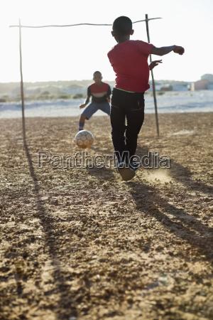 jungen fussball spielen zusammen in schmutz