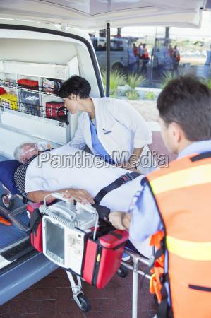 arzt untersucht patient auf ambulanz trage