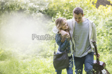 couple with guitar walking in park