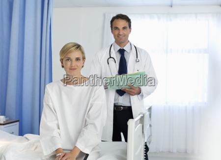 arzt und patient laechelnd im krankenzimmer