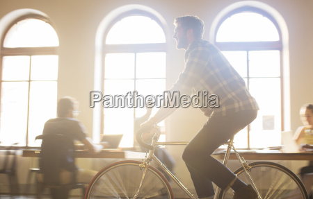 casual businessman riding bicycle in sunny