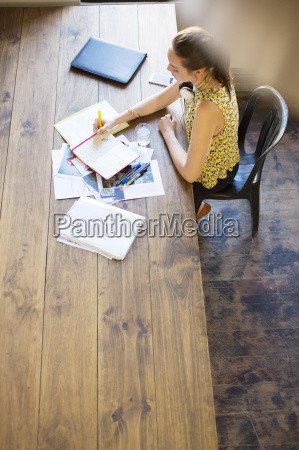 creative businesswoman writing in notebook at