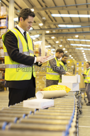 workers checking packages on conveyor belt
