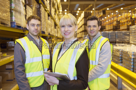 businesswoman and workers smiling in warehouse
