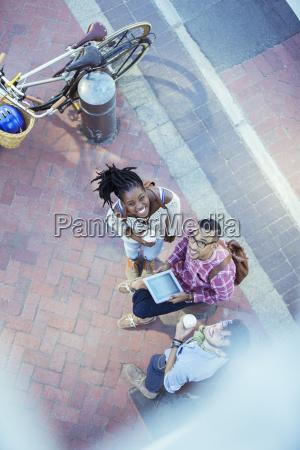 friends using digital tablet on city
