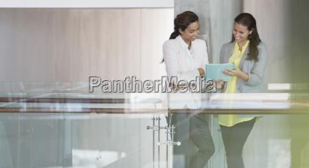 geschaeftsfrauen ueberpruefen papiere im buerokorridor