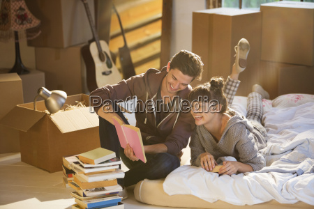 couple unpacking books in new home