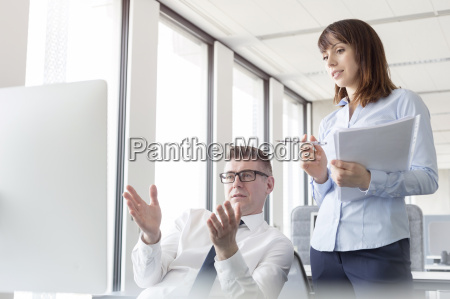 businessman at computer gesturing and explaining