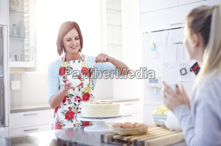 woman frosting cake baking in kitchen