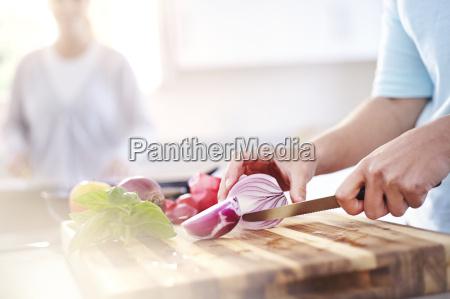 frau schneiden roten zwiebeln an bord