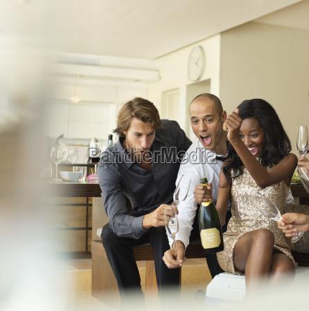 freunde flasche champagner oeffnen zusammen
