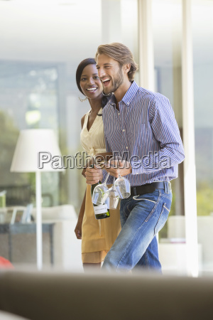 couple carrying wine bottle and glasses