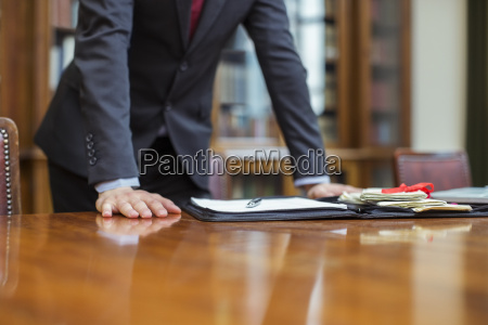 lawyer leaning on table in chambers