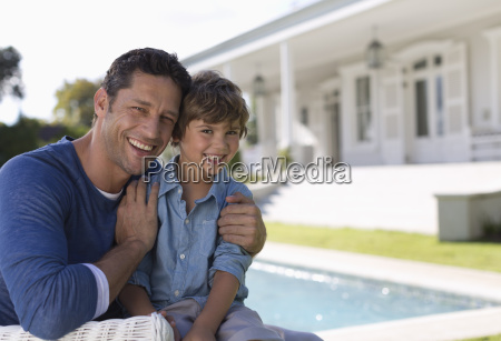 father and son smiling outside house