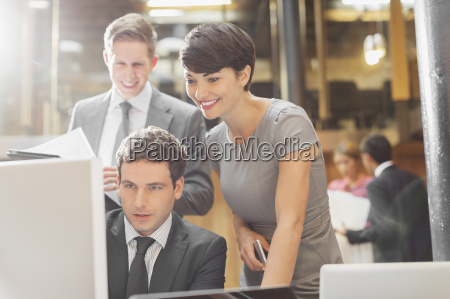 smiling business people working at computer
