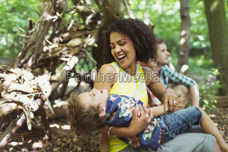 playful mother and son in woods